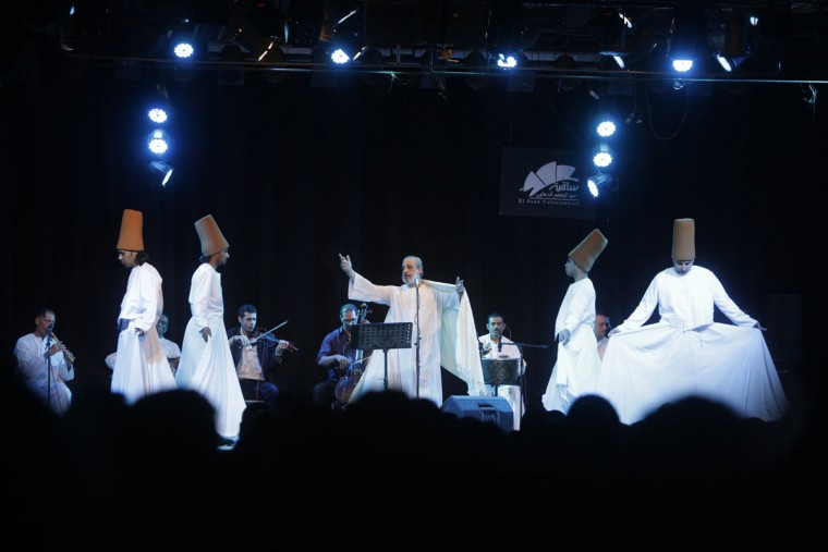 In this Thursday, May 28, 2015 photo, Amr el-Toney, center, founder of the Mawlawiyah dervish dance troupe, directs dervishes from the Al-Tannoura Egyptian Heritage Dance Troupe, at the El Sawy culture center in Cairo, Egypt. ìWe aim to keep the balance between the Sufi recitations and modern signing style, looking to leave our own heritage to the coming generations,î el-Toney says. ìAll of the words of our recitations are about loving God.î (AP Photo/Amr Nabil)