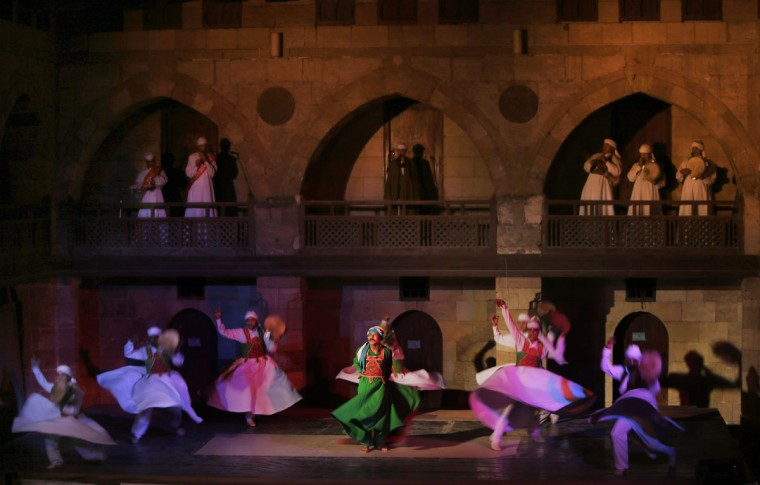 In this Saturday, May 30, 2015 photo, whirling dervishes from the Al-Tannoura Egyptian Heritage Dance Troupe spin during a performance at the 15th century El-Ghouri Palace, in Cairo, Egypt. Many visitors to Cairo are familiar with whirling dervishes - the stylized spinning dancers who perform across the city at cultural centers, cruise ships, hotels and weddings. The art form draws its roots from the ecstatic movements of Sufi Muslim mystics seeking a state of delirious oneness with God. (AP Photo/Amr Nabil)