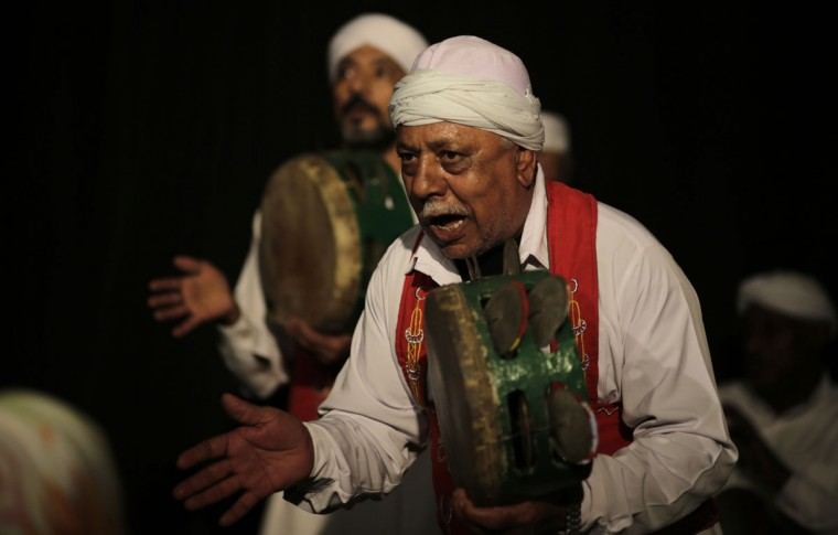 In this Thursday, April 30, 2015 photo, musicians play tambourines during a performance in collaboration with the Al-Tannoura Egyptian Heritage Dance Troupe at the ?El Dammah Theatre in Cairo, Egypt. Many visitors to Cairo are familiar with whirling dervishes as the stylized spinning dancers who perform across the city at cultural centers, cruise ships, hotels and weddings. The art form draws its roots from the ecstatic movements of Sufi Muslim mystics seeking a state of delirious oneness with God. (AP Photo/Amr Nabil)