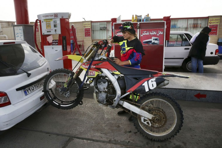 """In this photo taken Sunday, May 31, 2015, Behnaz Shafiei fills the tank of her motocross bike at a gas station near Hashtgerd, Iran, before a training session at a racetrack on the outskirts of the city, some 45 miles (73 kilometers) west of the capital, Tehran. """"When two days pass and I do not ride my motorcycle, I get really ill. Even the thought of not having a motorcycle some day gives me an awful feeling,"""" Shafiei said. (AP Photo/Vahid Salemi)"""