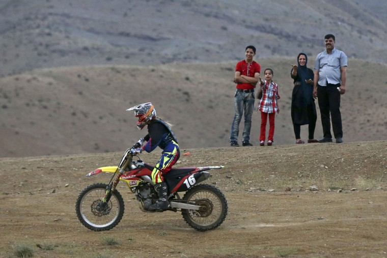 """In this photo taken Friday, June 5, 2015, fans watch Iranian Behnaz Shafiei ride her motocross bike during a training session at a racetrack in the Alborz mountain range near the village of Baraghan, some 19 miles (30 kilometers) west of the capital Tehran, Iran. """"My goal is to be a pioneer to inspire other women,î she said. ìTogether, we can convince authorities to recognize womenís motorcycle racing."""" (AP Photo/Vahid Salemi)"""
