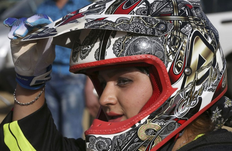 """In this photo taken Friday, June 5, 2015, Iranian motocross rider Behnaz Shafiei takes a break during a training session at a racetrack near the village of Baraghan, some 19 miles (30 kilometers) west of the capital Tehran, Iran. """"When two days pass and I do not ride my motorcycle, I get really ill. Even the thought of not having a motorcycle some day gives me an awful feeling,"""" Shafiei said. (AP Photo/Vahid Salemi)"""