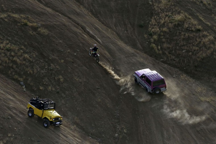 In this photo taken Friday, June 5, 2015, Iranian motocross rider Behnaz Shafiei ascends on a hill during her training session, while two vehicles drive off-road in the Alborz mountain range near the village of Baraghan some 19 miles (30 kilometers) west of the capital Tehran, Iran. For motocross rider Shafiei, she only set out to fly over the dirt hills of race tracks, but instead found herself jumping over the cultural and legal barriers woman face in the Islamic Republic. (AP Photo/Vahid Salemi)