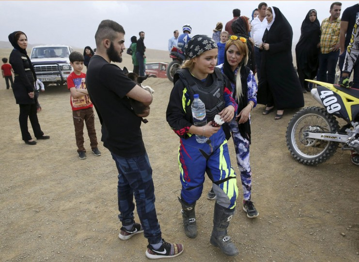 """In this photo taken Friday, June 5, 2015, Elma Ajdari, center right with sunglasses, talks to motocross rider Behnaz Shafiei during Shafiei's training session at a racetrack near the village of Baraghan, some 19 miles (30 kilometers) west of the capital Tehran, Iran. """"My goal is to be a pioneer to inspire other women,î she said. ìTogether, we can convince authorities to recognize women's motorcycle racing."""" (AP Photo/Vahid Salemi)"""