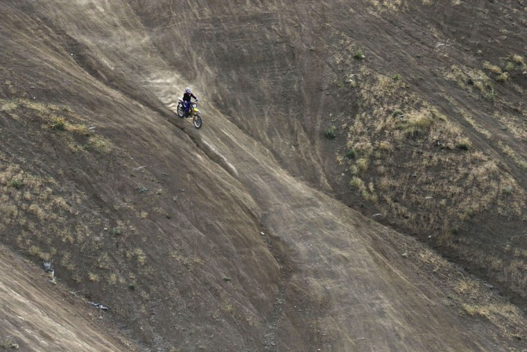 In this photo taken Friday, June 5, 2015, Iranian motocross rider Behnaz Shafiei descends on a hill during her training session near the village of Baraghan, some 19 miles (30 kilometers) west of the capital Tehran, Iran. (AP Photo/Vahid Salemi)
