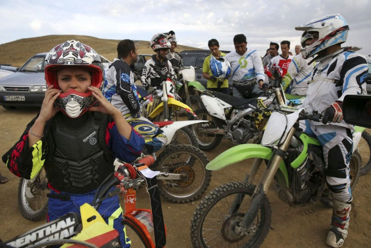 In this photo taken Friday, June 5, 2015, Iranian motocross rider Behnaz Shafiei, left, puts on her helmet in front of a group of men during a training session near the village of Baraghan, some 19 miles (30 kilometers) west of the capital Tehran, Iran. (AP Photo/Vahid Salemi)