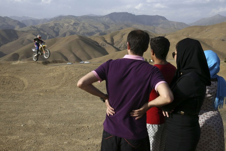 In this photo taken Friday, June 5, 2015, fans watch Iranian motocross rider Behnaz Shafiei take to the air during her training session near the village of Baraghan some 19 miles (30 kilometers) west of the capital Tehran, Iran. (AP Photo/Vahid Salemi)