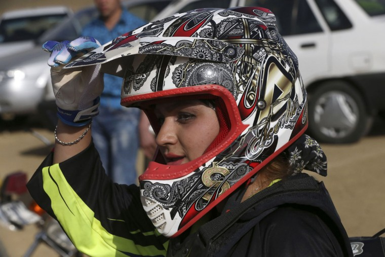 In this photo taken Friday, June 5, 2015, Iranian motocross rider Behnaz Shafiei takes a break during a training session at a racetrack near the village of Baraghan, some 19 miles (30 kilometers) west of the capital Tehran, Iran. (AP Photo/Vahid Salemi)