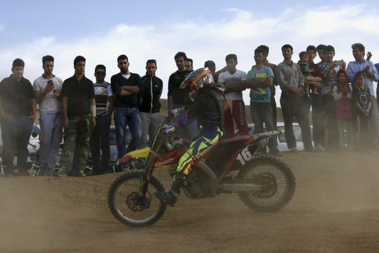 In this photo taken Friday, June 5, 2015, fans watch Iranian Behnaz Shafiei ride her motocross bike during her training session at a racetrack near the village of Baraghan, some 19 miles (30 kilometers) west of the capital Tehran, Iran. (AP Photo/Vahid Salemi)