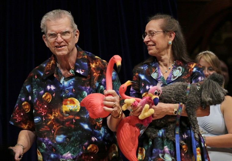 Artist Don Featherstone, 1996 Ig Nobel Prize winner and creator of the plastic pink flamingo lawn ornament, poses with his wife Nancy while being honored as a past recipient during a performance at the Ig Nobel Prize ceremony at Harvard University, in Cambridge, Mass. Featherstone died Monday, June 22, 2015, at an elder care facility in Fitchburg, Mass., according to his wife, Nancy. He was 79. (AP Photo/Charles Krupa)
