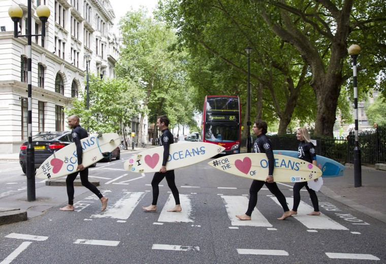 Climate change campaigners in wetsuits holding surfboards cross the road by the Houses of Parliament in London, ahead of a mass lobby to urge members of parliament to back strong action on climate change. (Justin Tallis/Getty Images)