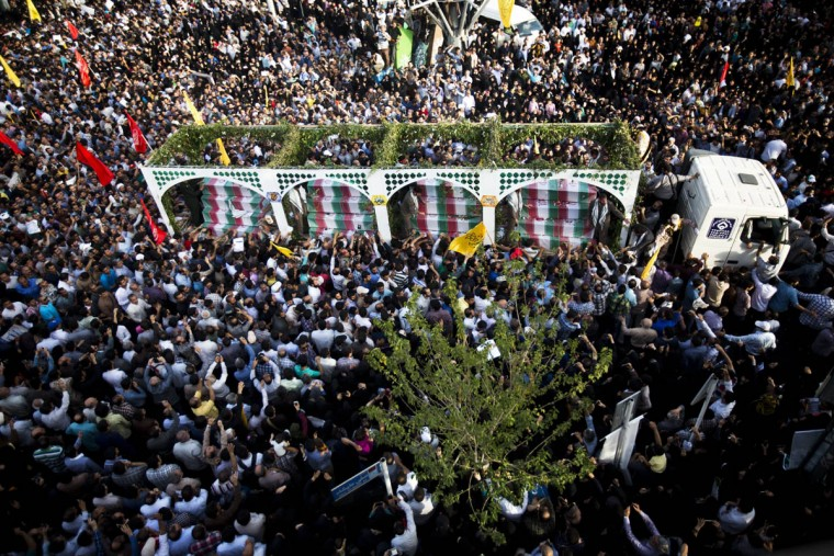 Iranians follow a truck carrying coffins towards Tehran's Baharestan square during a funeral procession for 270 victims of the Iran-Iraq war (1980-1988) (175 of them belonging to a group of military divers), a month after their bodies have been repatriated in Iran. The divers were responsible for breaking the enemy lines during an operation in 1986 with the aim of taking Basra in southern Iraq, but the operation was discovered by the Iraqi army that killed a large number of Iranian military and made others as prisoners. (Behrouz Mehri/Getty Images)
