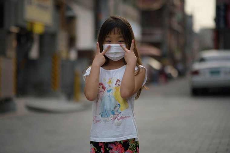 Mask wearer Choi Lin, 7, poses for a photo on a street in the Sinchon area of Seoul. As the death toll from MERS mounts in South Korea, face masks are an increasingly common sight, as they are in other parts of east Asia during flu season, but some health experts doubt they do much more than provide reassurance to the wearer. (Ed Jones/Getty Images)