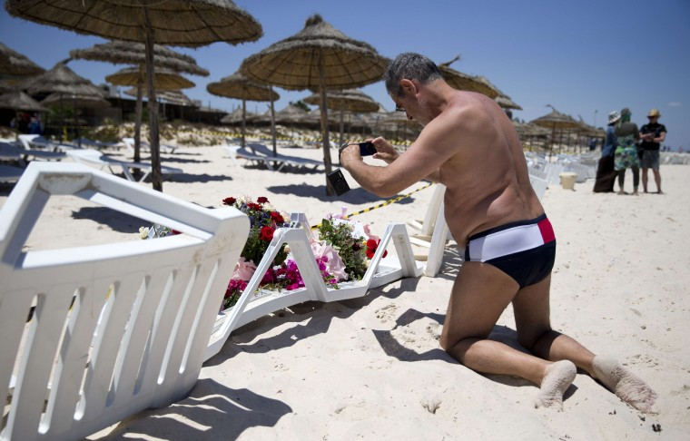 A man uses a phone to take pictures of flowers at the site of a shooting attack on the beach in front of the Riu Imperial Marhaba Hotel in Port el Kantaoui, on the outskirts of Sousse south of the capital Tunis. The Islamic State (IS) group claimed responsibility on June 27 for the massacre in the seaside resort that killed nearly 40 people, most of them British tourists, in the worst attack in the country's recent history. (Kenzo Tribouillard/AFP-Getty Images)