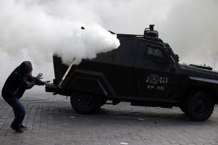 A police vehicle sprays tear gas as a protester throws a stick at it during a march demanding more participation in the education reform discussions, in Santiago, Chile. Teachers began on June 1 an indefinite strike in protest against the newest education reforms that are being discussed in Congress and promoted by Chile's President Michelle Bachelet's government. (Luis Hidalgo/Associated Press)