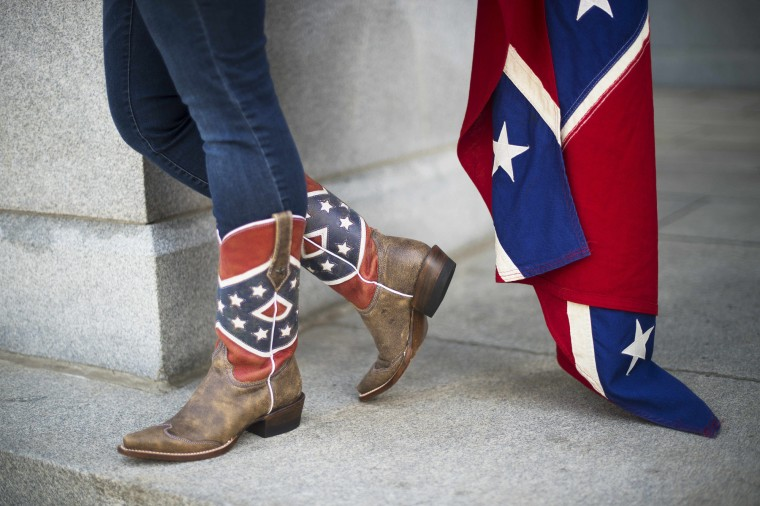 "Pro-confederate flag demonstrators Alice Horky wears confederate flag cowboy boots as she protests atop the South Carolina State House steps in Columbia, South Carolina. There has been a growing clamor for the flag -- branded ""a reminder of systemic oppression and racist subjugation"" by President Barack Obama on Friday -- to be removed from the grounds of the state house in Columbia. Once flown by the rebel army of the slave-owning South, the confederate flag is seen by some as a symbol of regional heritage, but by many more as an ugly reminder of racism's cruel legacy. (Jim Watson/AFP-Getty Images)"