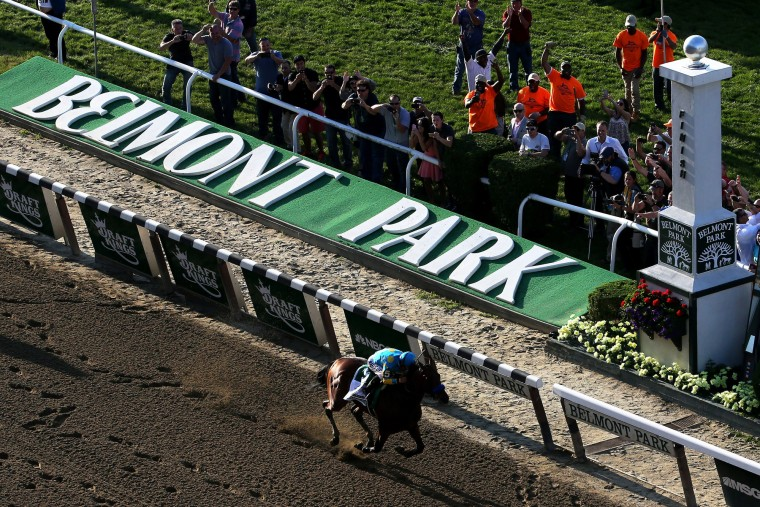 American Pharoah #5, ridden by Victor Espinoza, crosses the finish line to win the 147th running of the Belmont Stakes at Belmont Park on June 6, 2015 in Elmont, New York. (Mike Stobe/Getty Images)