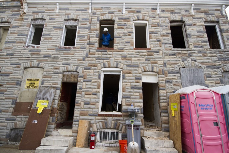 Details employees begin deconstructing the homes in the 900 block of N. Port Street. (Kalani Gordon, Baltimore Sun)