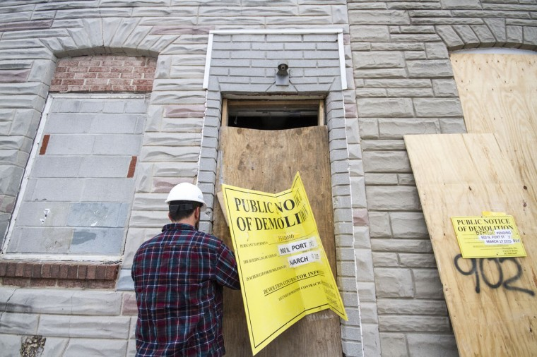 Max Pollock, the materials manager for Details, takes off the board covering the doorway of a vacant home at the south end of the 900 block of N. Port Street.