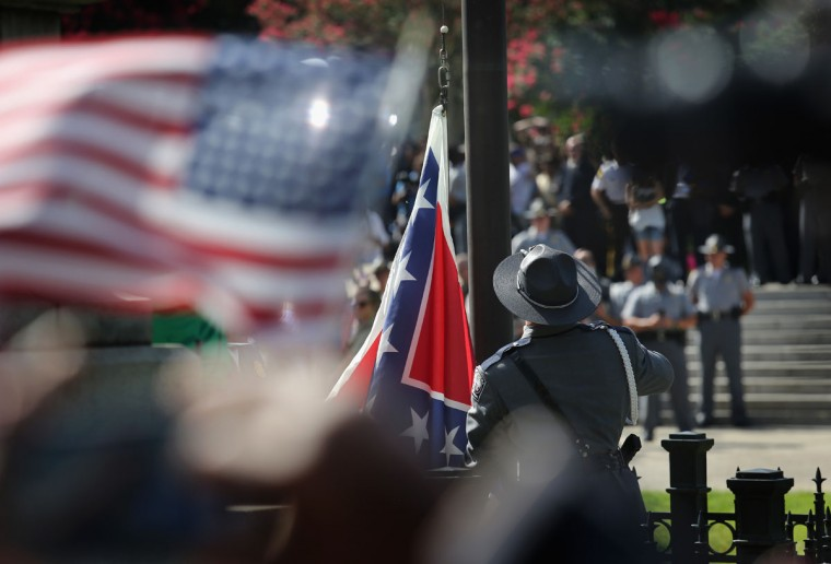 A South Carolina state police honor guard lowers the Confederate flag from the Statehouse grounds on July 10, 2015 in Columbia, South Carolina. Republican Governor Nikki Haley presided over the event after signing the historic legislation to remove the flag the day before. (Photo by John Moore/Getty Images)