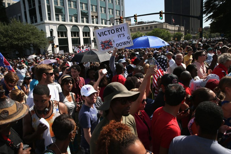 A crowd watches after a South Carolina honor guard lowers the Confederate flag from the Statehouse grounds on July 10, 2015 in Columbia, South Carolina. Republican Governor Nikki Haley presided over the event after signing the historic legislation to remove the flag the day before. (Photo by John Moore/Getty Images)