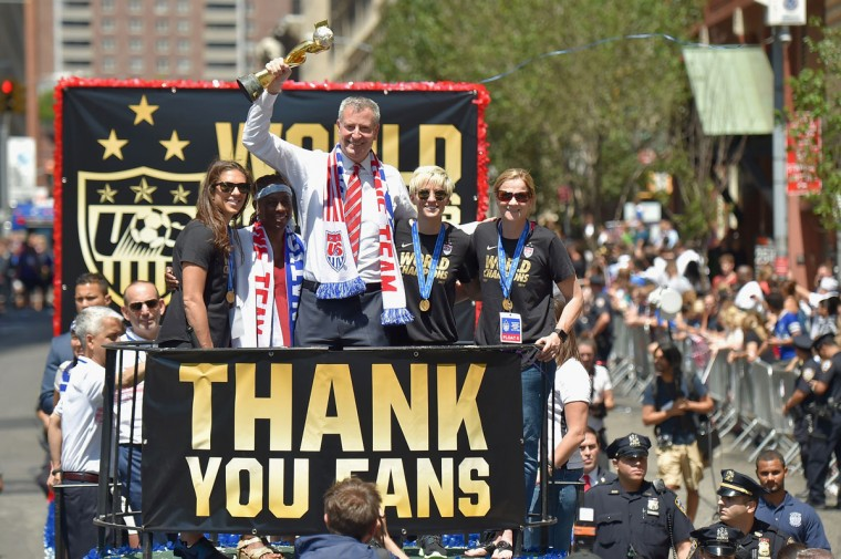 Soccer player Carli Lloyd, Chirlane McCray, Mayor Bill de Blasio, soccer player Megan Rapinoe, and U.S. Coach Jill Ellis aboard a float in the New York City Ticker Tape Parade for World Cup Champions U.S. Women's Soccer National Team on July 10, 2015 in New York City. (Photo by Michael Loccisano/Getty Images)