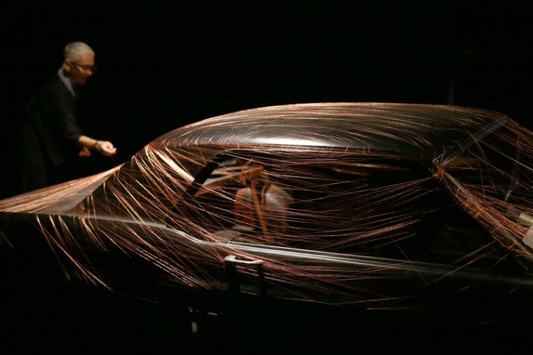 "An artists' assistant wraps a car in cotton thread during a press preview for an exhibition by French-British artist Alice Anderson entitled ""Memory Movement Memory Objects"" at the Wellcome Collection on Tuesday in London. The exhibition, which is due to run from Wednesday through Oct. 18, showcases work where Anderson has entirely mummified everyday objects in copper thread. (Carl Court/Getty Images)"