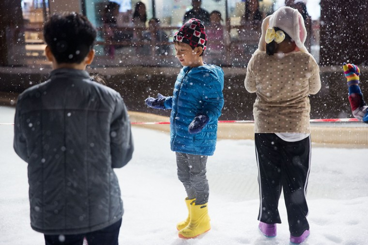 Children gather under a small artificial snowfall at Snow Town Bangkok on July 28, 2015 in Bangkok, Thailand. Over the last year, two new indoor cold weather venues, Snow Town and Harbin Ice Wonderland, have opened in Bangkok offering many Thais their first opportunity to visit a frozen, wintry landscape.  (Taylor Weidman/Getty Images)
