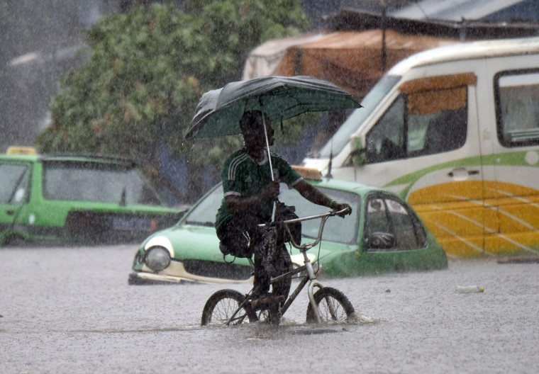 A man rides his bicycle under heavy rain in the neighborhood of Koumassi, in Abidjan on June 22, 2015. The high rain fall this month has killed at least 16 people in Abidjan. (AFP Photo/Sia Kambou)