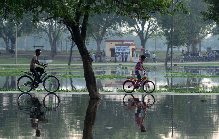 Indian children ride bicycles along a flooded pathway following heavy rain in Allahabad on June 30, 2014. (AFP Photo/Sanjay Kanojia)