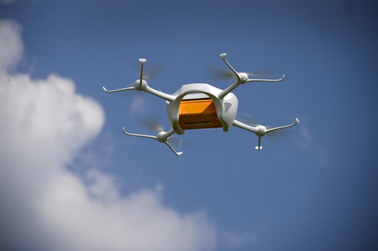 A drone carrying a mailbox of Swiss Post flies Tuesday above the airport of Bellechasse, western Switzerland during a news conference. Swiss Post started a series of test for parcel delivery by drone in the alpine country that has many isolated villages in valleys surrounded by mountains. (FABRICE COFFRINI/AFP/Getty Images)