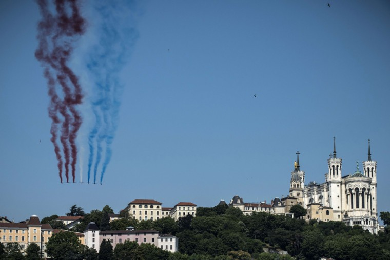 "Alphajet aircrafts from the French elite acrobatic flying team ""Patrouille de France"" release smoke the colors of the  French flag as they fly above Lyon, close to the Notre-Dame de Fourviere Basilica on Tuesday. (JEAN-PHILIPPE KSIAZEK/AFP/Getty Images)"