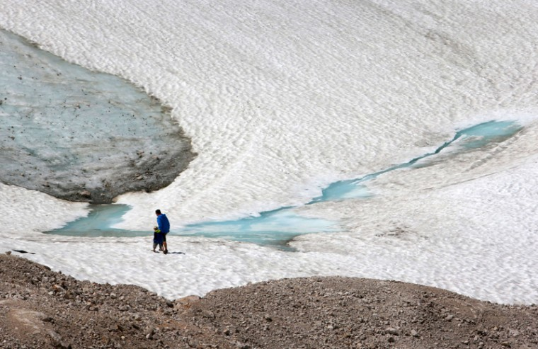 Two walkers make their way along the Schneeferner glacier at German highest mountain Zugspitze near Garmisch-Partenkirchen, southern Germany, on Tuesday. Temperatures at German highest peak on Tuesday climbed up to 20 degrees Celsius. (STEPHAN JANSEN/AFP/Getty Images)