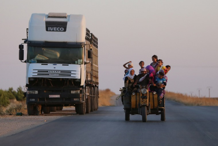 Syrians travel near the northeastern Syrian city of Hasakeh on Monday. Syrian regime forces took back several parts of a neighbourhood in Hasakeh from the Islamic State group on June 29, but heavy clashes continued, a monitor said. (YOUSSEF KARWASHAN/AFP/Getty Images)