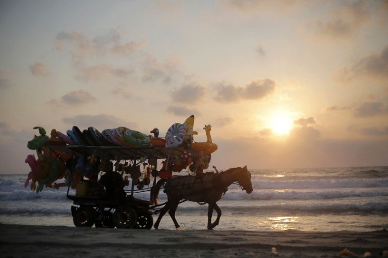 A Palestinian vendor rides his horse cart on the beach in Gaza City during the holy month of Ramadan on Monday. (MOHAMMED ABED/AFP/Getty Images)