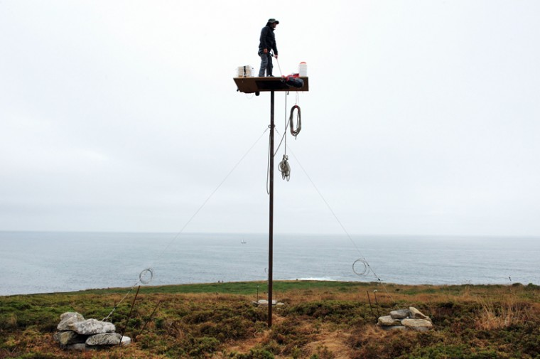 "French artist Abraham Poincheval stands atop a platform on a pole in Esquibien, western France on Tuesday, where he plans to remain for one week as part of a performance called ""La Vigie"" (The Look-out Post). (FRED TANNEAU/AFP/Getty Images)"