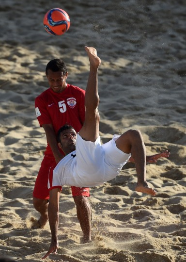 Iran's wing Mohammad Ahmadzadeh (R) kicks the ball past Tahiti's wing Raimoana Bennett during the FIFA Beach Soccer World Cup 2015 football match Iran vs Tahiti in Espinho on July 16, 2015. (Francisco Leong/AFP/Getty Images)
