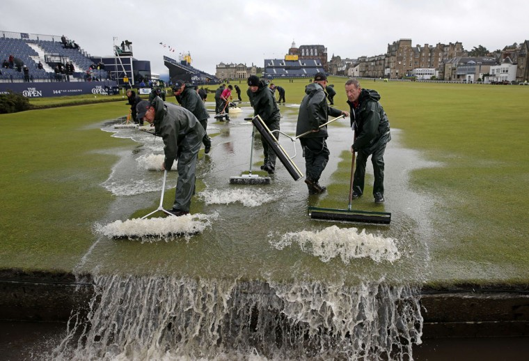 Groundsmen sweep water into the Swilcan Burn from the 1st fairway, after heavy rain make the course unplayable early on the second day of the 2015 British Open Golf Championship on The Old Course at St Andrews in Scotland, on July 17, 2015. By 8:00 p.m. large puddles had formed on the Old Course's fairways and greens as the deluge continued and director of greenkeeping Gordon Moir said that no time could yet be set for play to resume. (AFP Photo/Adrian Dennis)