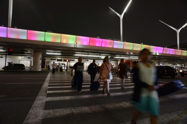 Pedestrians cross the street under a new mile-long programmable lightband is unveiled at Los Angeles International Airport. The polychromatic LED lightband, along with 91 new sculptural light poles, represent completion of Phase II of the airport's $118 milion facelift, which began last year. The unveiling's specially created light show was programmed with the colors of the Special Olympics World Summer Games, which open on July 25 in Los Angeles. (ROBYN BECK/AFP/Getty Images)