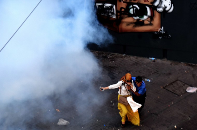 A man and a woman run away from tear gas during a demonstration on Monday in Istanbul following an explosion in Turkey's southern town of Suruc. A suspected Islamic State suicide bomber killed at least 31 people in an attack on a Turkish cultural center where activists had gathered to prepare for an aid mission in the nearby Syrian town of Kobane. (OZAN KOSE/AFP/Getty Images)