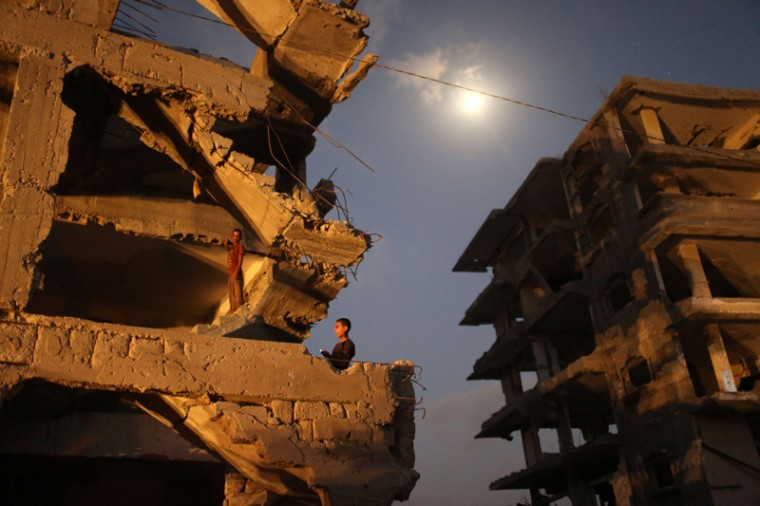 Palestinian boys stand inside their damaged home in al-Tufah, in the east of Gaza City on Monday during a power outage. Residents of Gaza, home to 1.8 million people, have been experiencing up to 15 hours of electricity outage a day for the past two weeks due to fuel and power shortages. (MAHMUD HAMS/AFP/Getty Images)