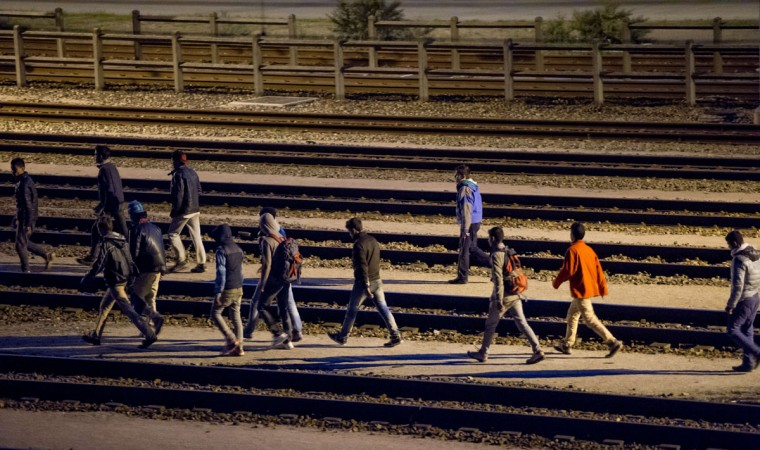 Migrants walk along railway tracks at the Eurotunnel terminal on July 28, 2015 in Calais-Frethun. (PHILIPPE HUGUEN/AFP/Getty Images)