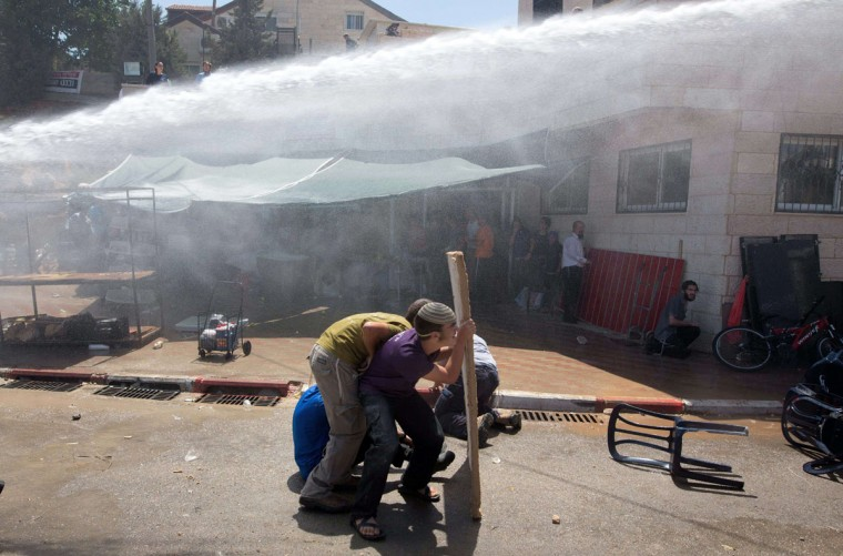 Israeli security forces spray a water cannon towards Israeli settlers during clashes as the demolition started of the so-called Dreinoff buildings under an Israeli High Court ruling in the settlement of Beit El, north of Ramallah in the occupied West Bank, on 29 July, 2015. (MENAHEM KAHANA/AFP/Getty Images)