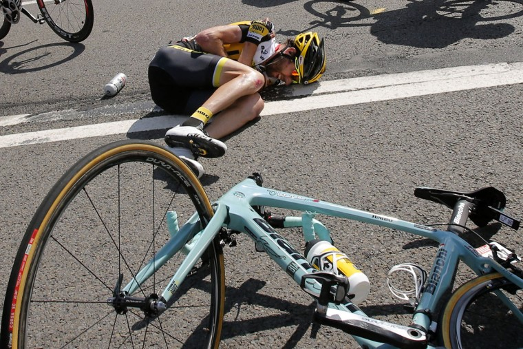 Laurens ten Dam of the Netherlands lies on the road after crashing with several of other riders during the third stage of the Tour de France cycling race over 159.5 kilometers (99.1 miles) with start in Antwerp and finish in Huy, Belgium, Monday, July 6, 2015. (AP Photo/Christophe Ena)