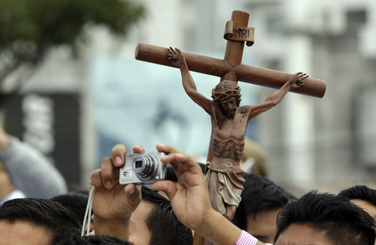 Backdropped by a crucifix, a seminarian reaches up to make a photo as he waits with other seminarians for the arrival of Pope Francis, at Christ the Redeemer square in Santa Cruz, Bolivia, Thursday, July 9, 2015. Hundreds of thousands packed the square and the streets beyond. Overnight, several thousand slept in square to get a spot close to the front. Francis arrived in the Andean nation late Wednesday after three days in Ecuador. (AP Photo/Gregorio Borgia)