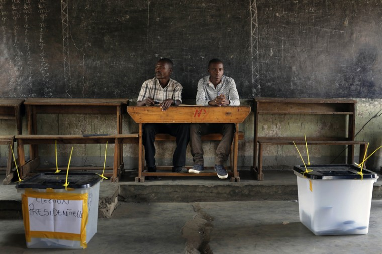 Election observers sit in an empty polling station for the presidential elections in Bujumbura, Burundi, on Tuesday. A low turnout was experienced in several polling stations in the Burundi's capital at the start of voting following a night of explosions and gunfire in at least two opposition strongholds that oppose President Pierre Nkurunziza''s candidacy for a third term in office. (Jerome Delay/AP)
