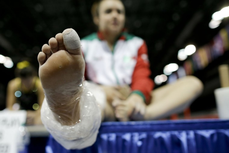 Mexico's Ana Lago sits with ice around her foot during a training session for the Pan Am Games women's artistic gymnastics competition in Toronto, Thursday, July 9, 2015. (AP Photo/Gregory Bull)