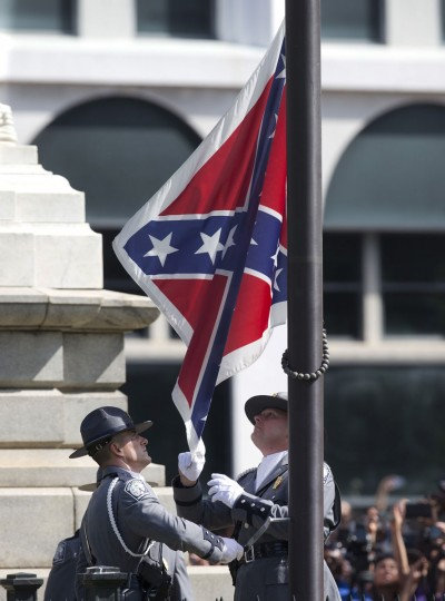 An honor guard from the South Carolina Highway patrol removes the Confederate battle flag from the Capitol grounds in Columbia, S.C., ending its 54-year presence there, on Friday, July 10, 2015. (AP Photo/John Bazemore)