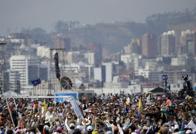 Pope Francis is surrounded by faithful as he arrives in his popemobile to celebrate Mass at Bicentennial Park in Quito, Ecuador, on Tuesday. Francis is making his first visit as pope to his Spanish-speaking neighborhood, traveling to three South American nations: Ecuador, Bolivia and Paraguay. (Gregorio Borgia/AP)