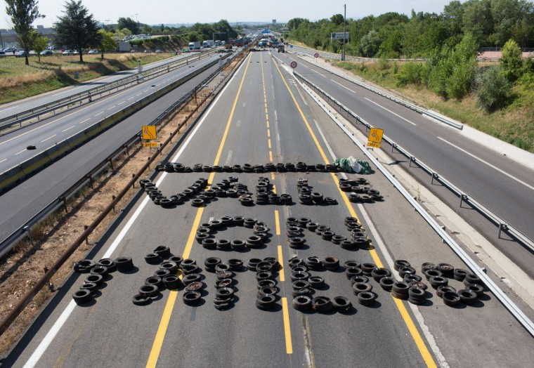 "Farmers use tires to write a message to French Prime Minister Manuel Valls : ""Valls, We Are Waiting For You"" on the highway between Paris and Lyon in Limonest near Lyon, central France, Thursday, July 23, 2015. Angry French farmers block the famed Mont Saint Michel causeway and highways leading to the Alps, hoping to get more government help for margins they say are being chipped way by cheap imports and pressure from grocery chains. Thursday's protests were a rejection of the government offer to back loans to the farmers and delay tax payments as part of a 600 million euro plan. (AP Photo/Vincent Dargent)"